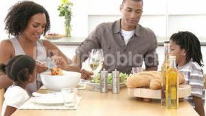 Family eating pasta and salad at home