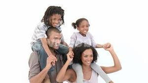 AfroAmerican parents giving their son and daughter piggyback rides