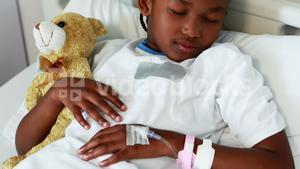 Sick girl resting with teddy bear on bed