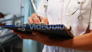 Female doctor writing on a clipboard