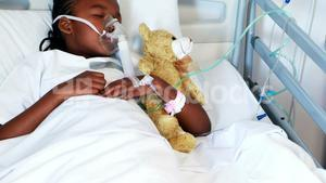 Sick girl in oxygen mask resting with teddy bear