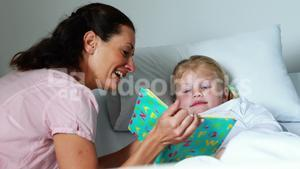 Girl on bed reading book with her mother