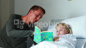 Girl on bed reading book with her father