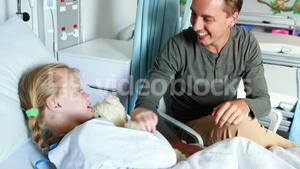 Father giving teddy bear to her sick daughter