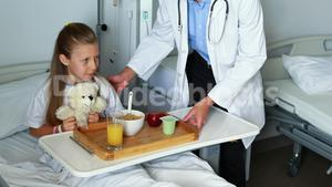 Doctor serving food to sick girl