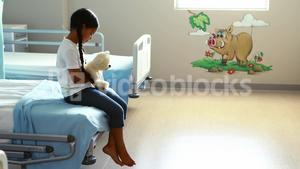 Sick girl sitting on bed with teddy bear