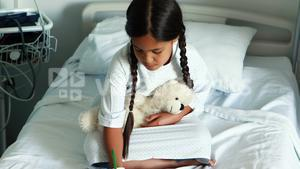 Girl drawing picture in a book