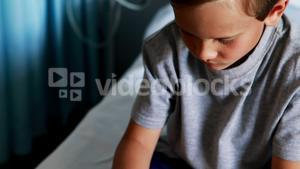 Boy using digital tablet on bed