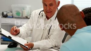 Male doctor discussing medical report with patient