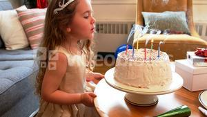 Girl blowing candles on birthday cake