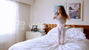 Girl playing on bed in bedroom
