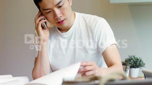 Man looking at document while talking on mobile phone