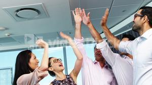 Executives giving high five in office