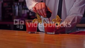 Bartender pouring cocktail into glass at bar counter in bar