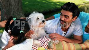 Family enjoying together with their pet dog in park