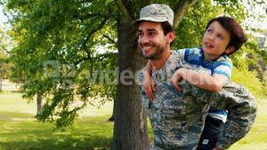 Smiling army soldier giving piggyback ride his son in park