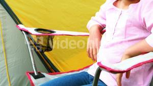 Smiling girl sitting in chair by tent at campsite in park