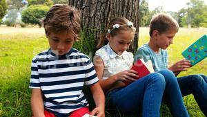 Kids reading books in park
