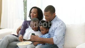 AfroAmerican young family watching television