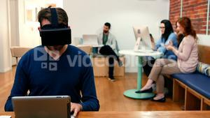 Male executive wearing virtual reality headset while using digital tablet
