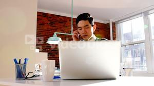 Male executive talking on mobile phone while using laptop