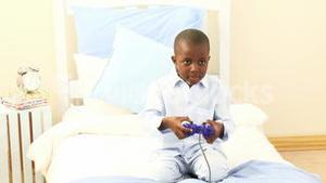AfroAmerican little kid playing video games in his bedroom