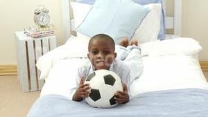 Panorama of AfroAmerican little kid playing with a soccer ball in hid bedroom