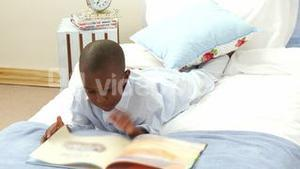 AfroAmerican smiling little boy reading in bed