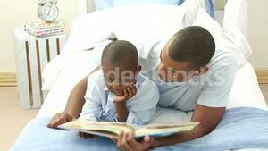 AfroAmerican little boy reading a book with his father in bed
