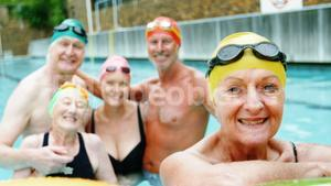 Senior citizens smiling in swimming pool