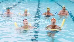 Portrait of senior citizens swimming with inflatable tube