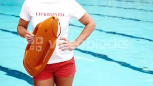 Portrait of female lifeguard standing at poolside