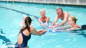 Swim trainer assisting seniors in swimming