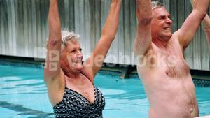 Seniors performing exercise in swimming pool