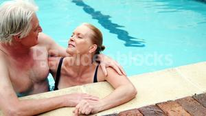 Senior couple embracing romancing in pool
