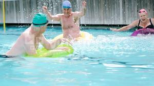 Seniors with inflatable tubes enjoying in pool
