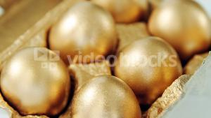 Close-up of golden Easter eggs in egg carton