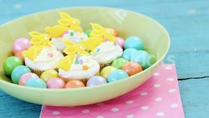 Colorful chocolate Easter eggs with cup cakes in bowl