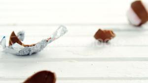 Broken chocolate Easter eggs falling on wooden surface