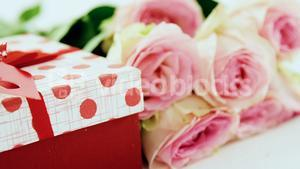 Gift box with bunch of rose on white background