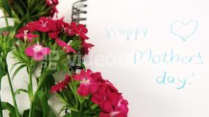 Pink flowers with text happy mothers day message on spiral book