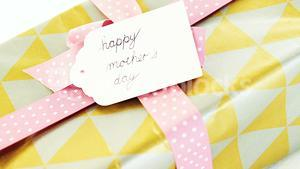 Gift box with happy mothers day tag on white background