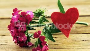 Bunch of pink flowers on wooden plank