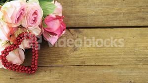 Bunch of pink roses on wooden plank