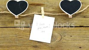 Black hearts and envelope with I love u mom card hanging on rope