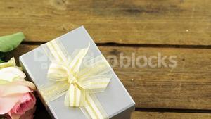 Gift box with bunch of rose on wooden plank