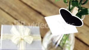 Gift box and flower vase on wooden plank