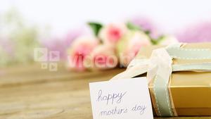Gift box with happy mother day card on wooden surface