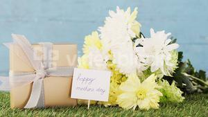 Gift box, happy mother day tag and flowers on grass
