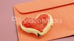 Happy mother day card, heart shape cookie on red envelope against pink background